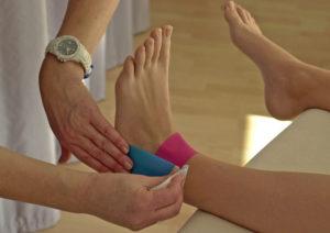 Detailaufnahmen eines linken Fußes an dem Medical Tape angebracht wird